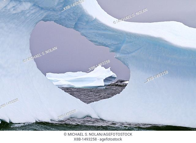Unusual window formation in iceberg with another iceberg in the background on the western side of the Antarctic Peninsula during the summer months