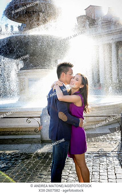 Couple getting wet next to a water fountain in Saint Peter's square. Vatican, Rome, Italy
