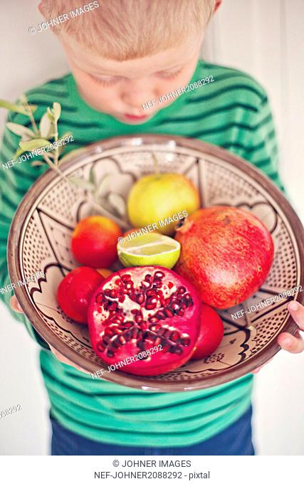 Boy holding bowl with fruits