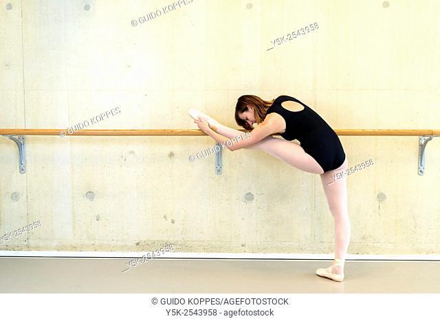 Arnhem, Netherlands. Young brunette ballet dancer training and rehearsing classical ballet in her ballet studio