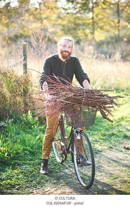 Young man carrying bunch of sticks on bicycle