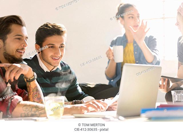 Creative young business people working at laptop