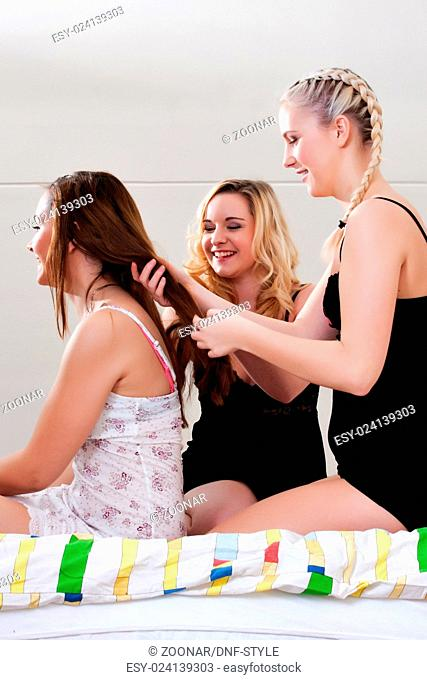 girs doing each others hair on bed