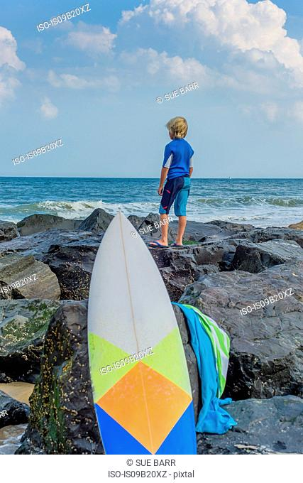 Young boy standing on rocks by sea, looking at view, surfboard in foreground