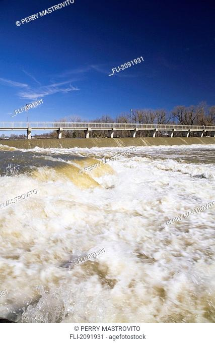 Footbridge and dam over the mille-iles river with a high water level in spring, terrebonne lanaudiere quebec canada