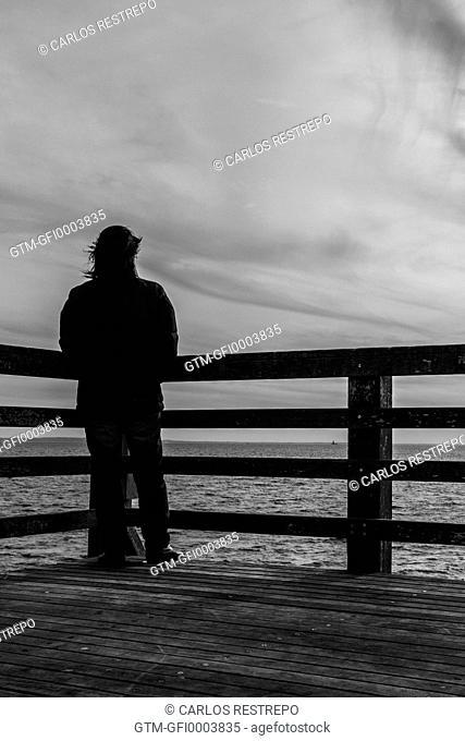 Solitary woman at a pier pensive in contemplation