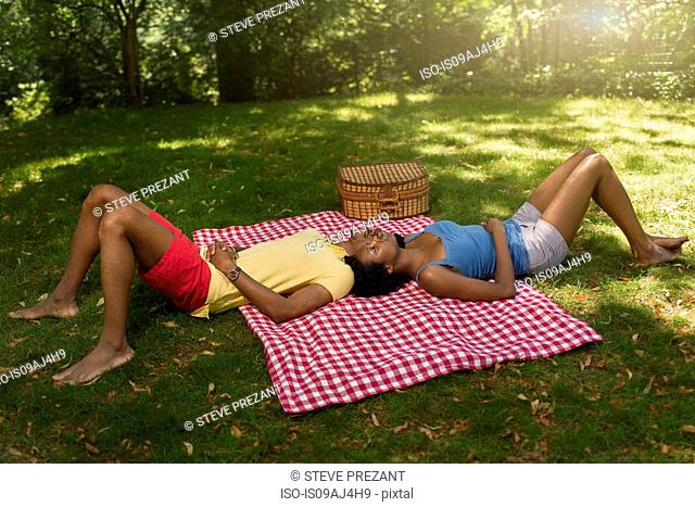 Young couple lying on picnic blanket in park on opposite sides