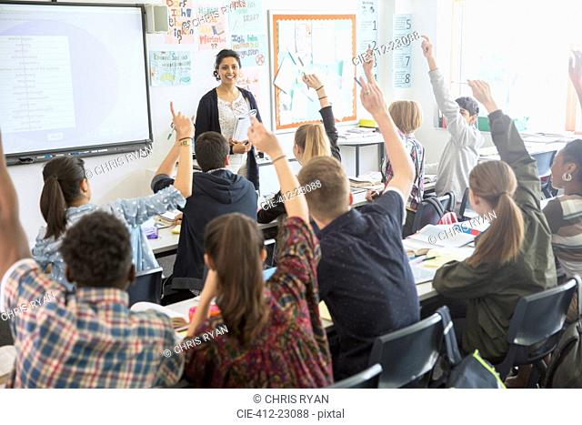 Rear view of teenage students raising hands in classroom