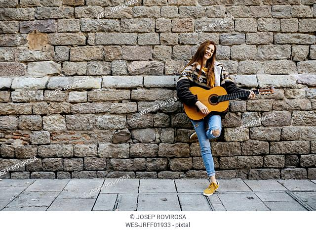 Red-haired woman playing the guitar in the city