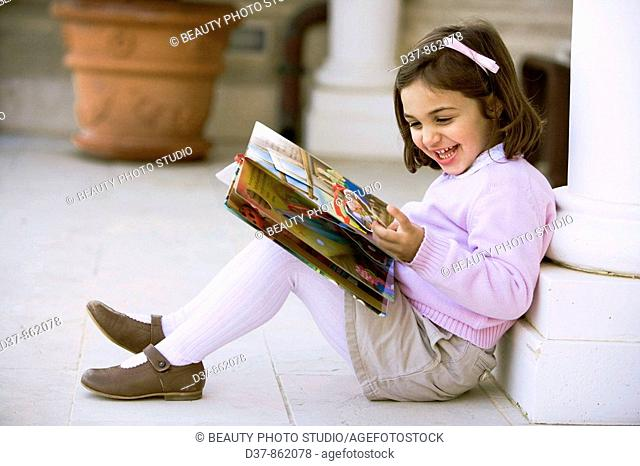 Little girl reading a book at home