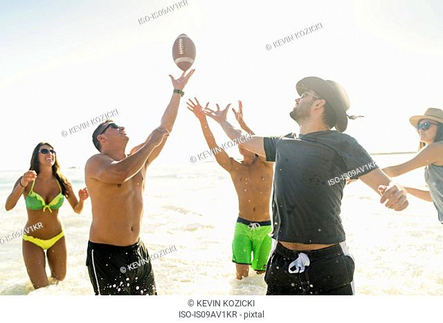 Male and female adult friends playing American football in sea at Newport Beach, California, USA