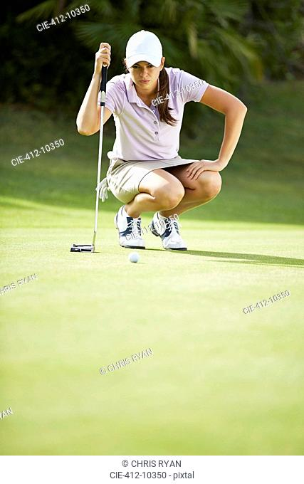 Woman preparing to putt on golf course