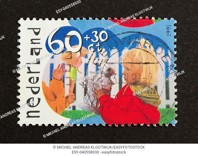 HOLLAND - CIRCA 1990: Stamp printed in the Netherlands shows two children trading toys, circa 1990
