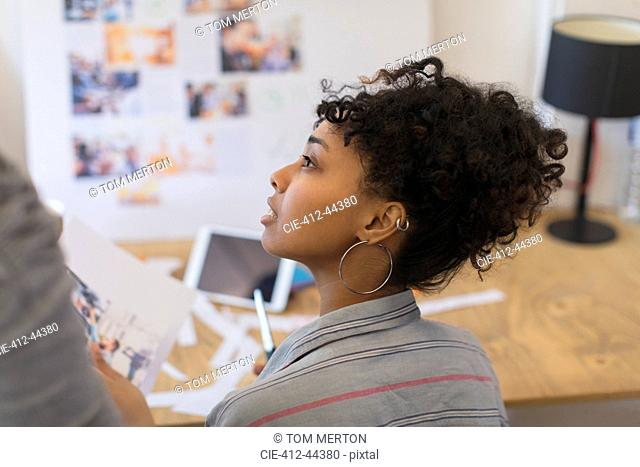 Attentive creative female designer reviewing proofs in office