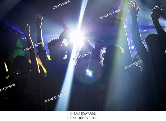 Spotlight over crowd dancing on dance floor