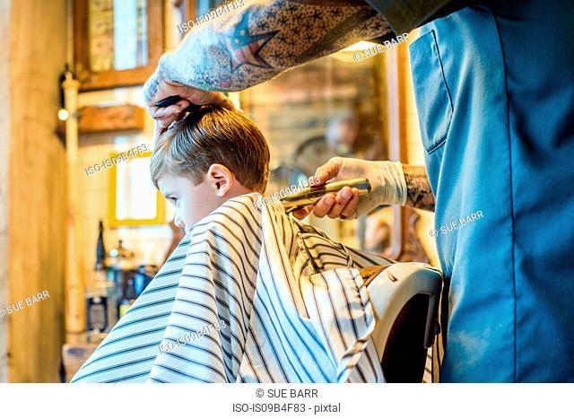 Barber shaving boy's hair