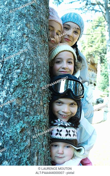 Kids and teens peeking from behind tree in ski clothes, portrait