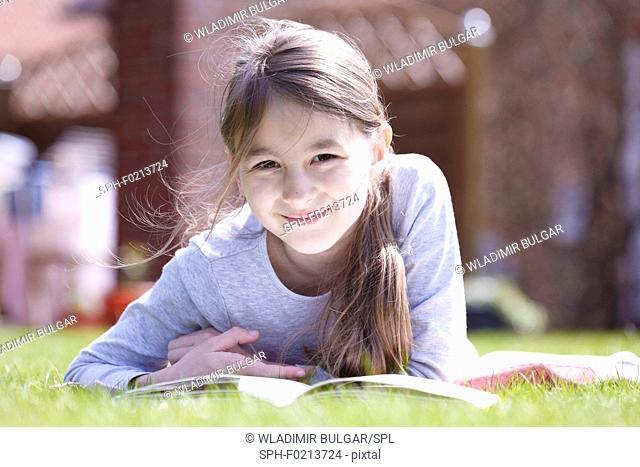 Girl lying on grass reading