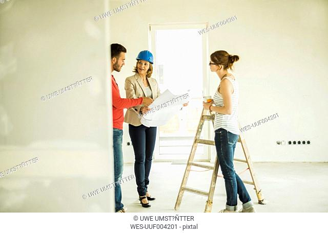 Architect showing construction plan to young couple