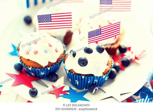 independence day, celebration, patriotism and holidays concept - close up of glazed cupcakes or muffins decorated with american flags and blueberries on plate...