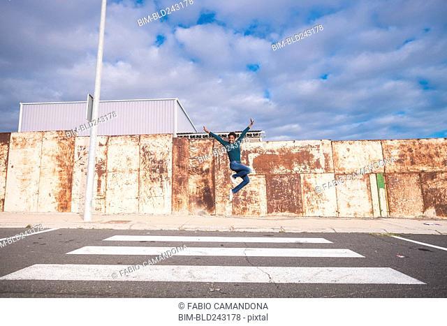 African American woman jumping for joy in crosswalk