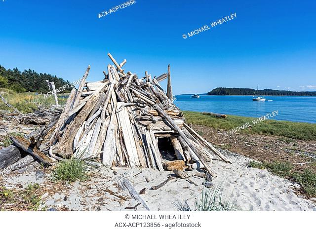 Driftwood shelter on beach, Jáji7em and Kw'ulh Marine Provincial Park, aka Sandy Island Marine Provincial Park, British Columbia, Canada