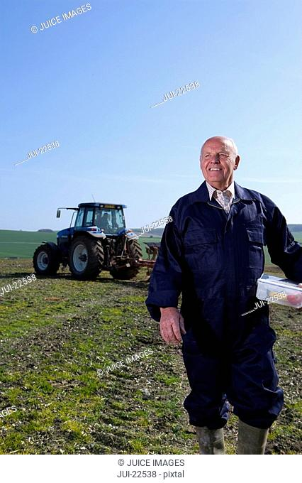 Smiling farmer holding lunchbox in field with tractor and plough in background