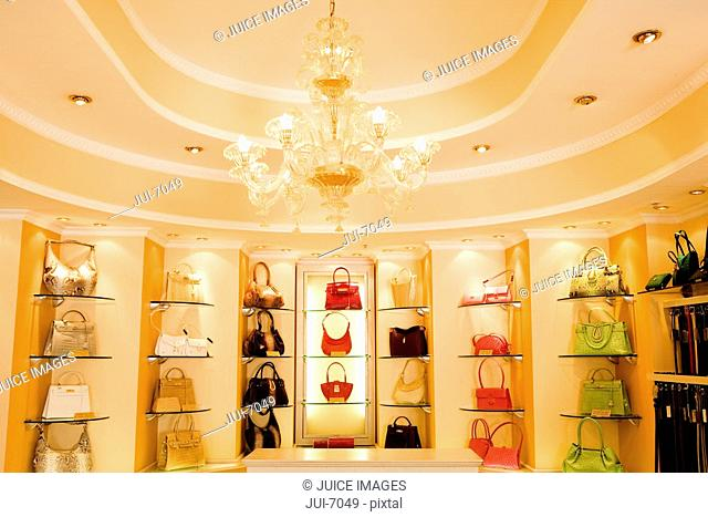 Selection of designer handbags on shelf display in glamorous boutique