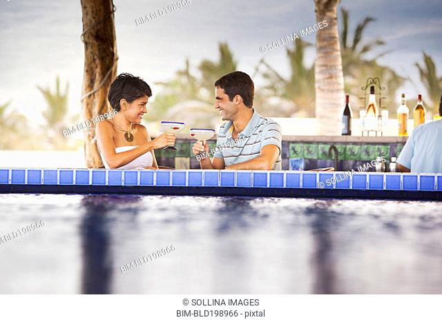 Hispanic couple drinking cocktails at poolside