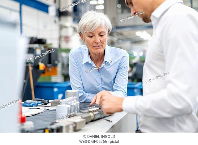 Businessman and senior businesswoman examining workpiece in a factory