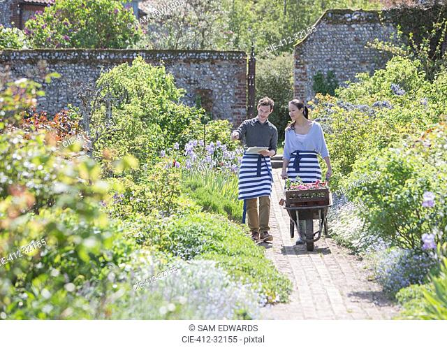 Plant nursery workers pushing wheelbarrow in sunny garden