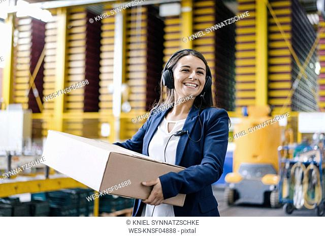 Young woman working at parcel service, carrying parcel in warehouse