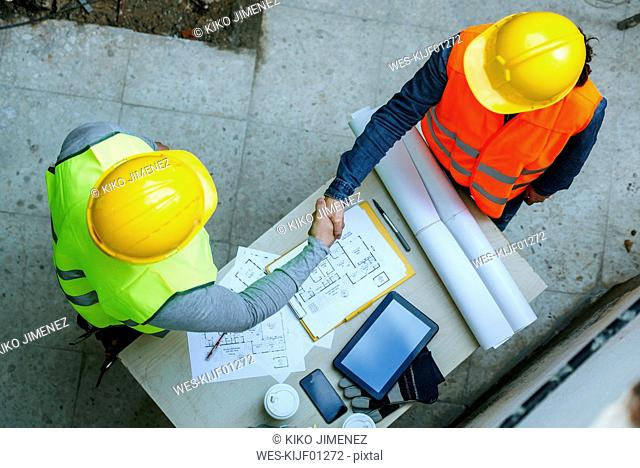 Woman and man in workwear shaking hands above construction plan