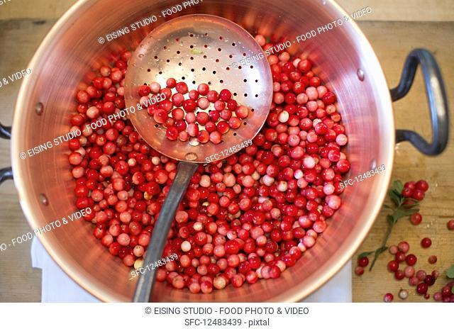 Lingon berry jam being made, raw lingon berries in a pot with draining spoon