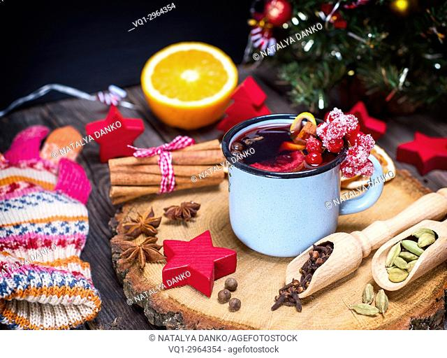 Mulled wine in an iron blue mug and drink ingredients among the Christmas decorations