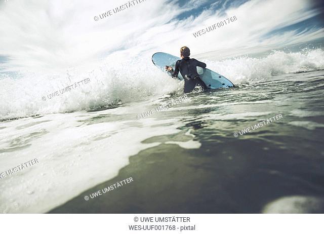 France, Bretagne, Camaret sur Mer, Teenage boy surfing at Atlantic coast