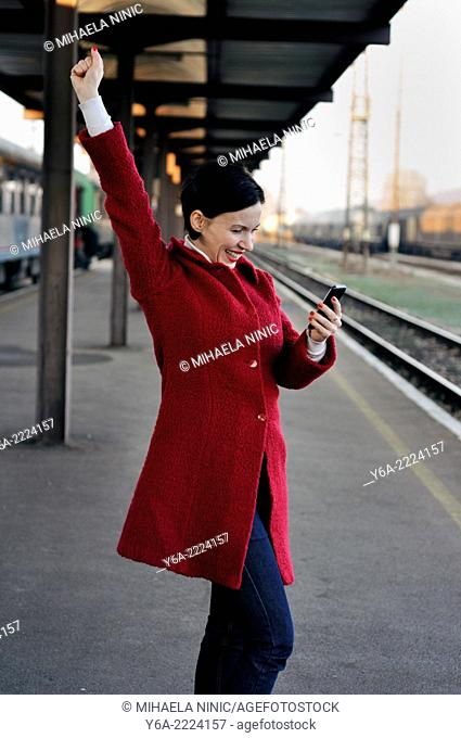 Happy mid adult woman looking at her mobile phone