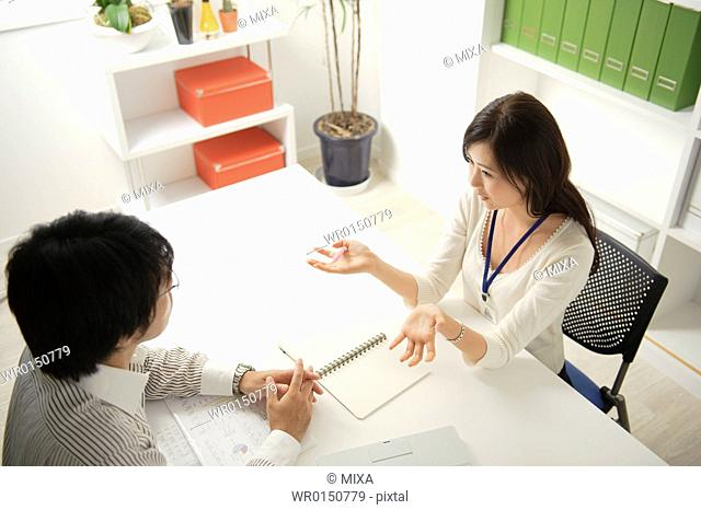 Two business people meeting at table
