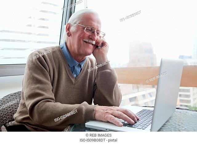 Senior man using mobile phone and laptop at home