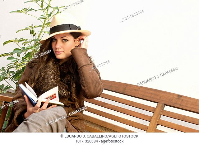 Fashionable girl with Panama hat reading a book outdoors