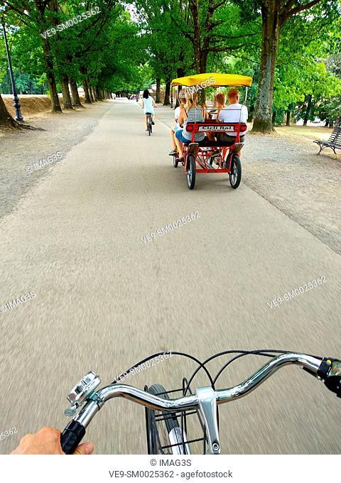 Cycling along Via delle Mura Urbane Street, Lucca, Tuscany, Italy