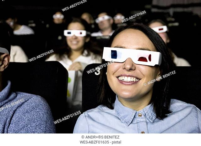 Woman with 3d glasses watching a movie in a cinema