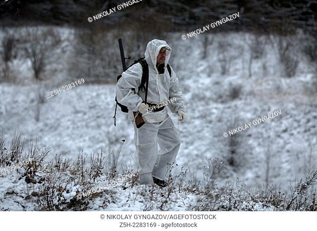 Hunter in white camouflage suit