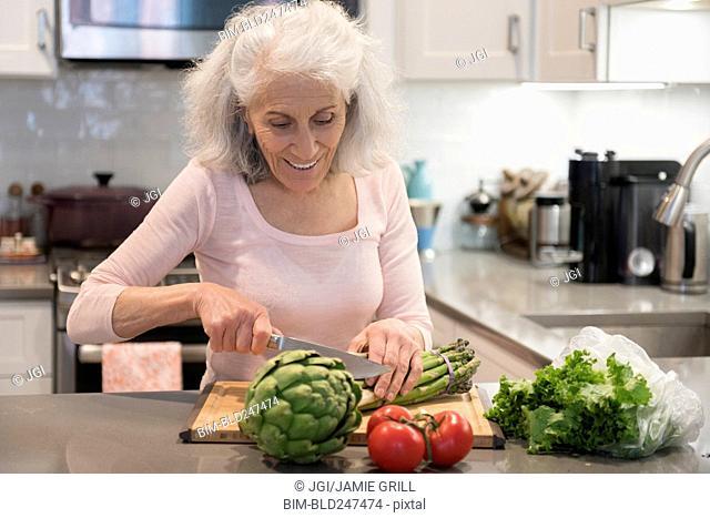 Older woman chopping asparagus