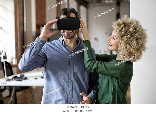 Happy woman and man with Virtual Reality Glasses in office