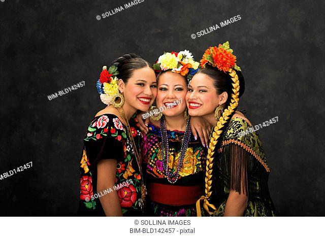 Hispanic teenage girls smiling in Sinaloa, Chiapas and Jallisco Folkloric dress