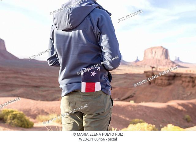 USA, Utah, back view of young man with folded American flag in his pocket at Monument Valley