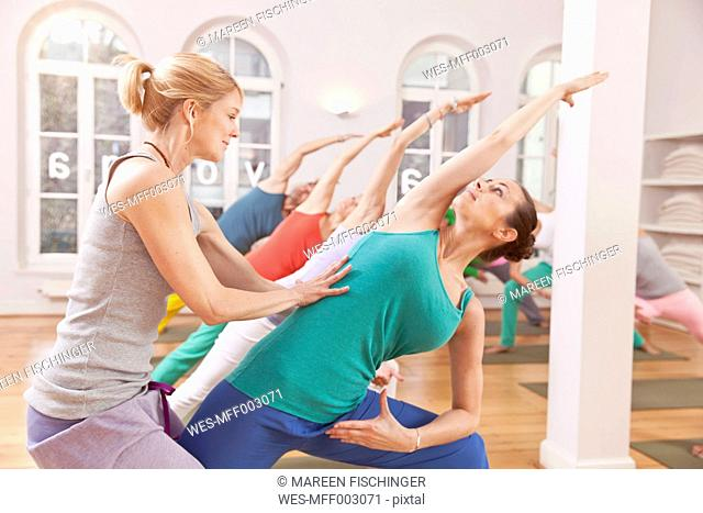 Yoga instructor helping people reach a triangle pose in studio
