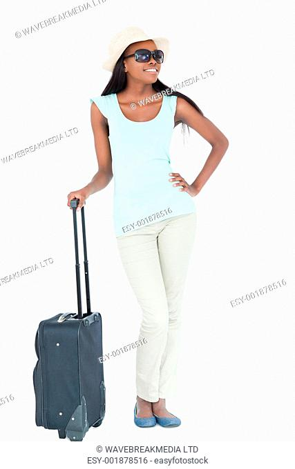 Happy smiling young woman with her suitcase against a white background