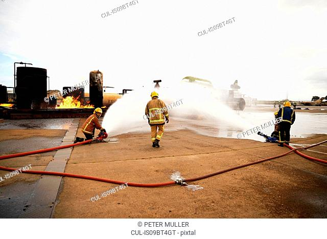 Firemen training, spraying water onto fire at training facility